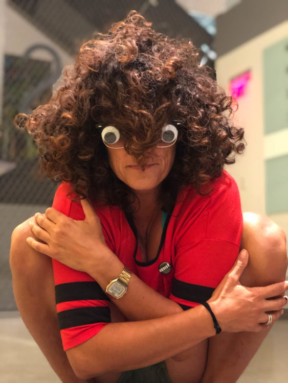 Woman with wild hair, arms crossed, and googly eyes stuck to her glasses in a deep squat, emanating light and exuberance