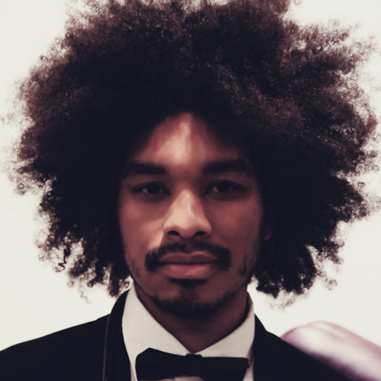 A black man with a large curly afro, wearing a black tuxedo with a white dress shirt and black bow tie. A black cord-like necklace hangs from his neck.